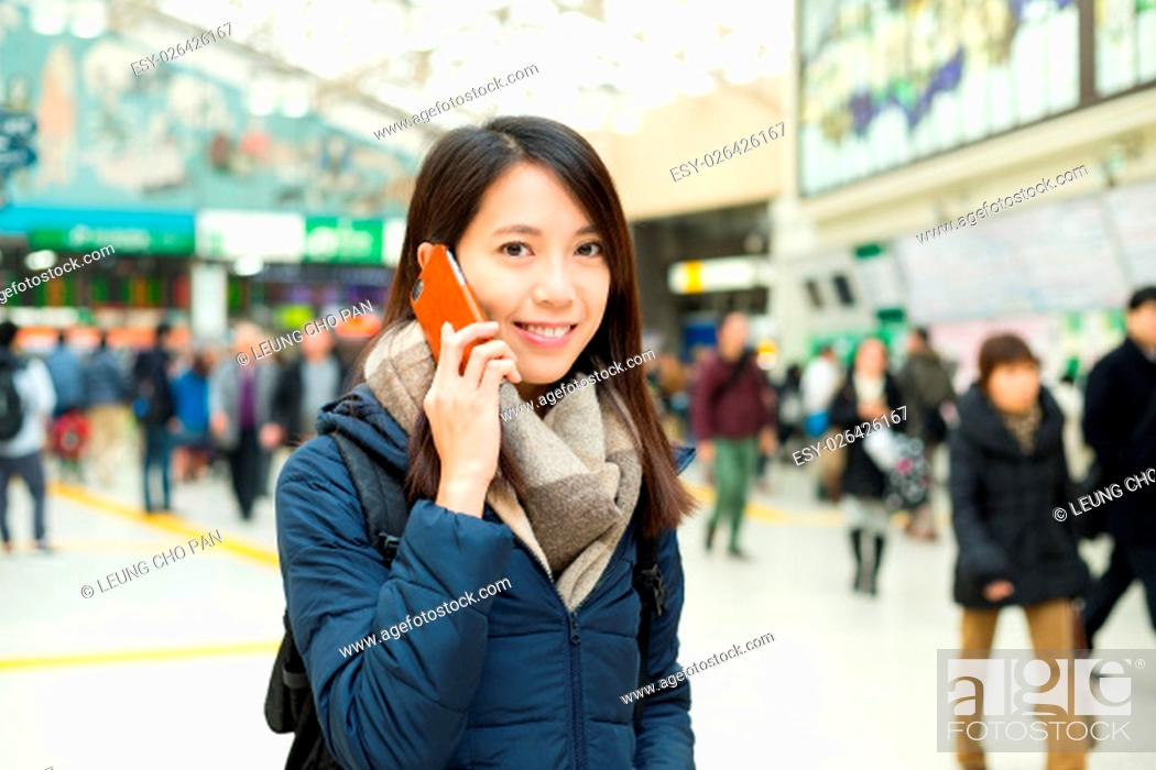 Stock Photo: Woman talk to mobile phone at train station.