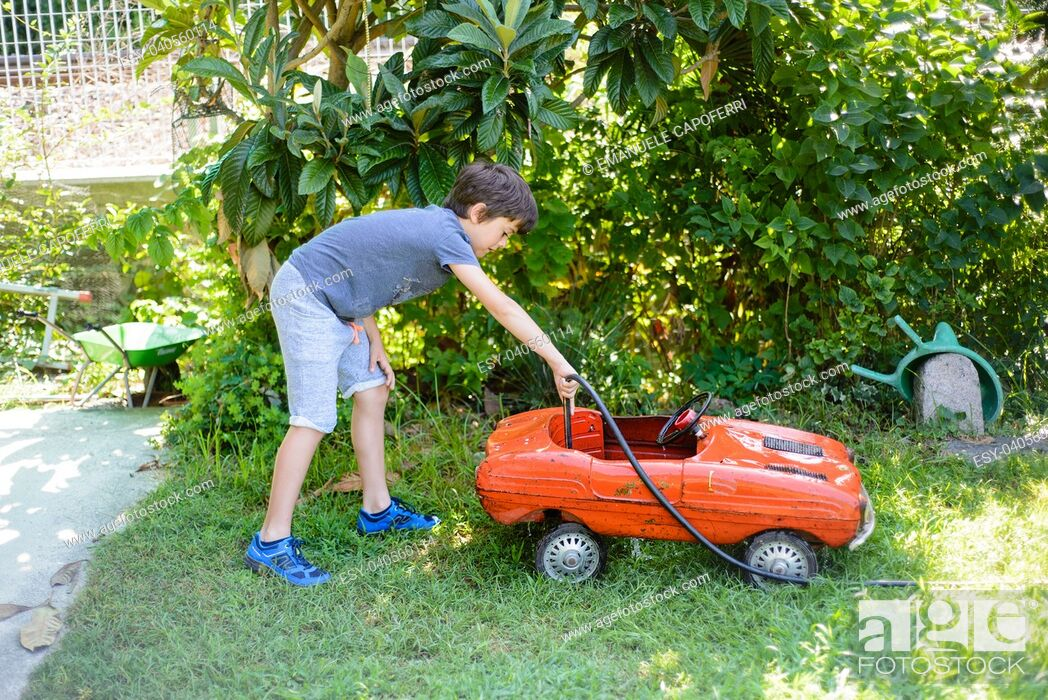 Stock Photo: child cleans red tin toy car in the garden.