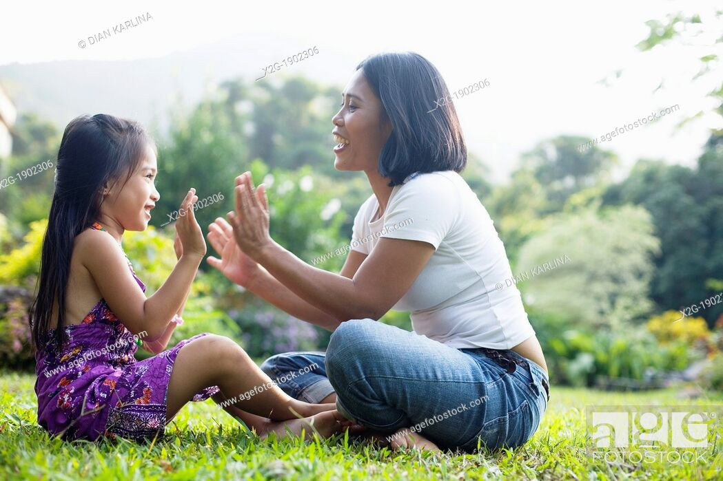 Stock Photo: China, Hong Kong, Mother and daughter (8-9) playing in garden.