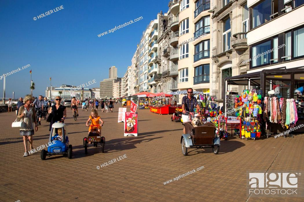 Stock Photo: Man on bicycle with cart and Golden Retriever dog in it on the beach promenade, Ostend, Flanders, Flemish Region, Belgium.