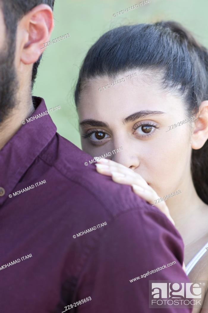 Stock Photo: Young Middle Eastern woman hiding behind her man outdoors.