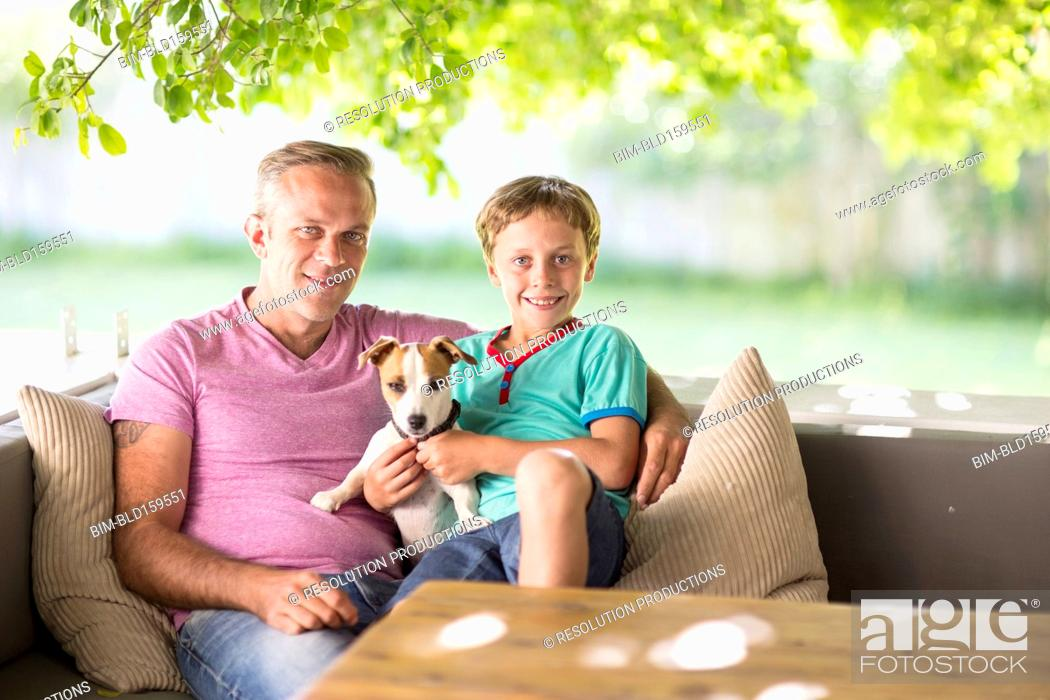 Stock Photo: Caucasian father and son sitting with dog on sofa.