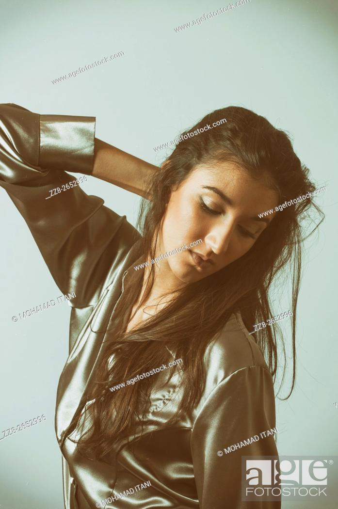 Stock Photo: Young woman hand on head looking down.
