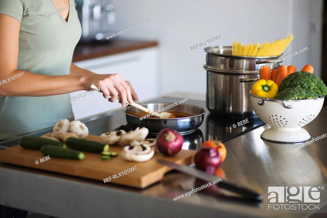 Stock Photo: Young woman in kitchen, cooking pasta sauce, cutting board with vegetables.