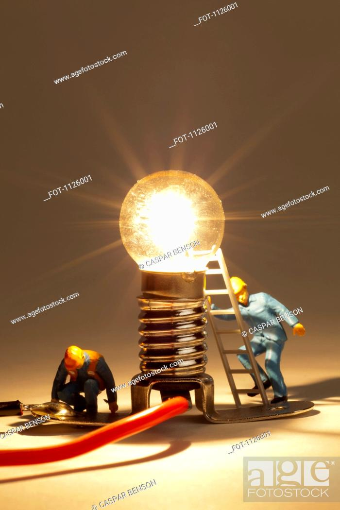Stock Photo: Miniature electrician figurines working on an illuminated light bulb.