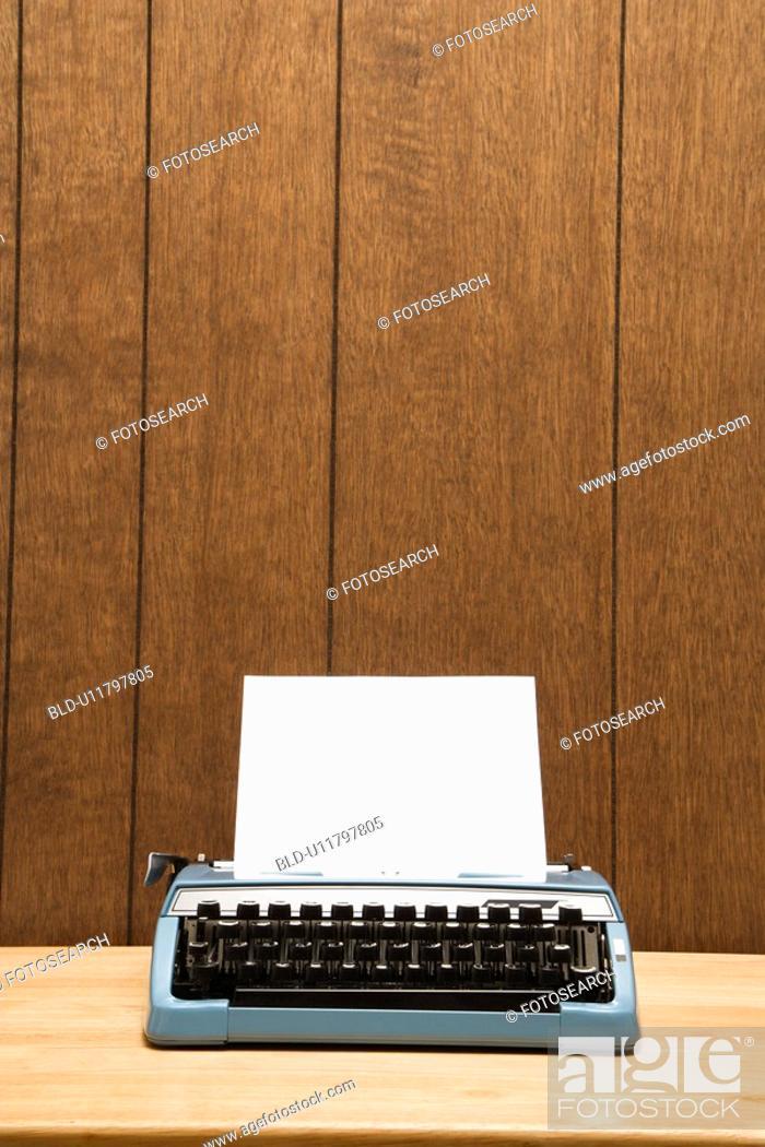 Stock Photo: Vintage blue typewriter on desk with wood paneling.