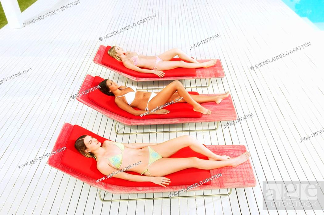 Stock Photo: Young women sunbathing on deckchairs by swimming pool high angle view.