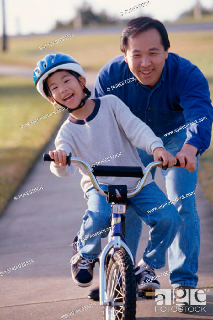 Stock Photo: Portrait of a father helping his son ride a bicycle.