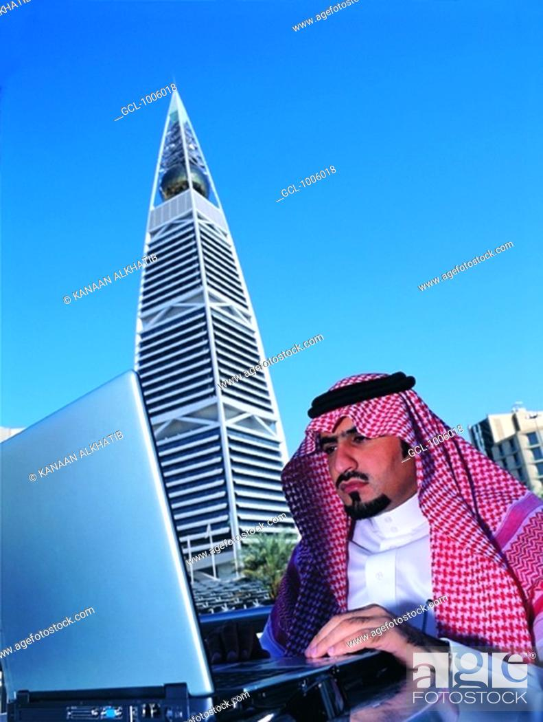 Stock Photo: Saudi Businessman working on Laptop near Faisaliah Tower in Riyadh, Saudi Arabia.