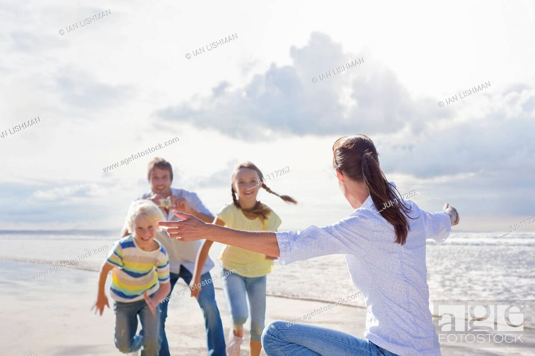 Imagen: Family Taking Photos On Beach Vacation Together.
