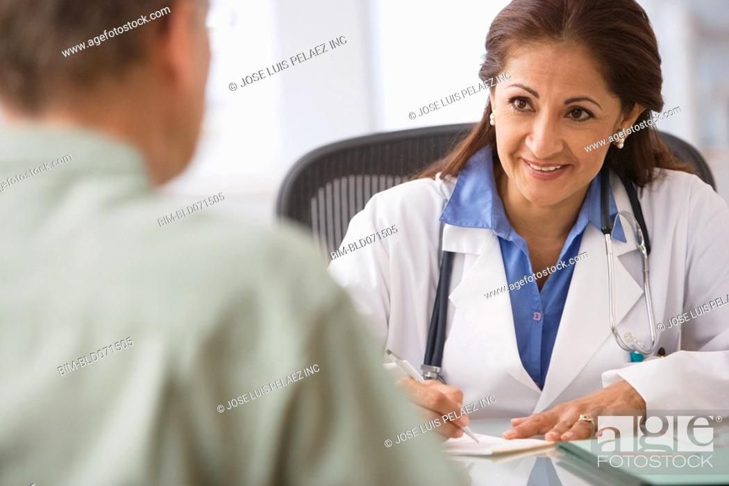Stock Photo: Hispanic female doctor talking to patient.
