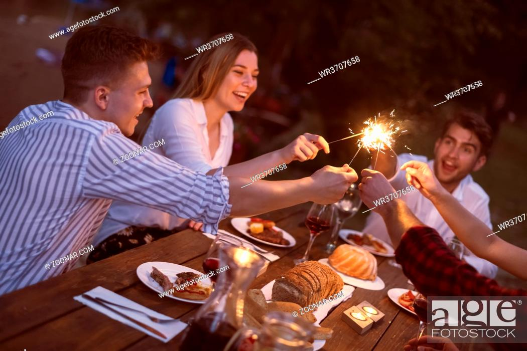 Stock Photo: group of friends toasting red wine while having picnic or french dinner party on summer holiday vacation near the river at night.