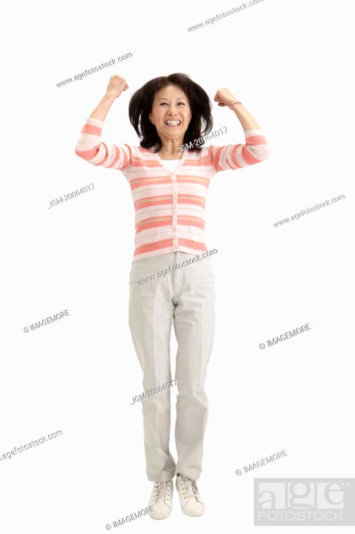 Stock Photo: Wife, Woman jumping with arms raised and laughing.