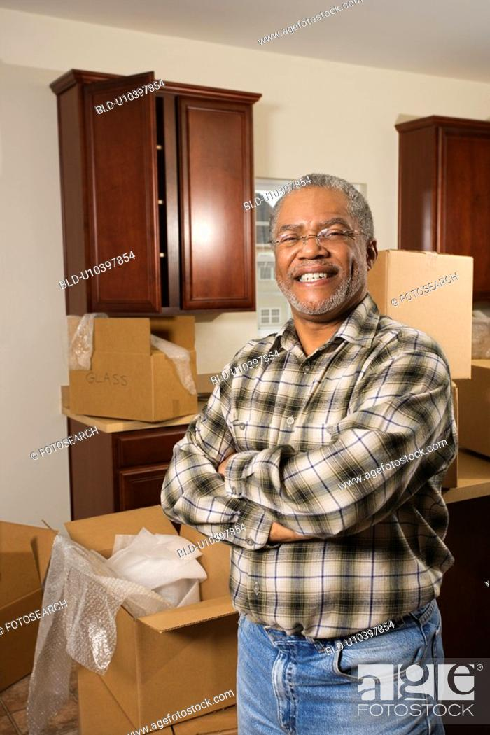Stock Photo: Portrait of middle-aged African-American male in kitchen with moving boxes.