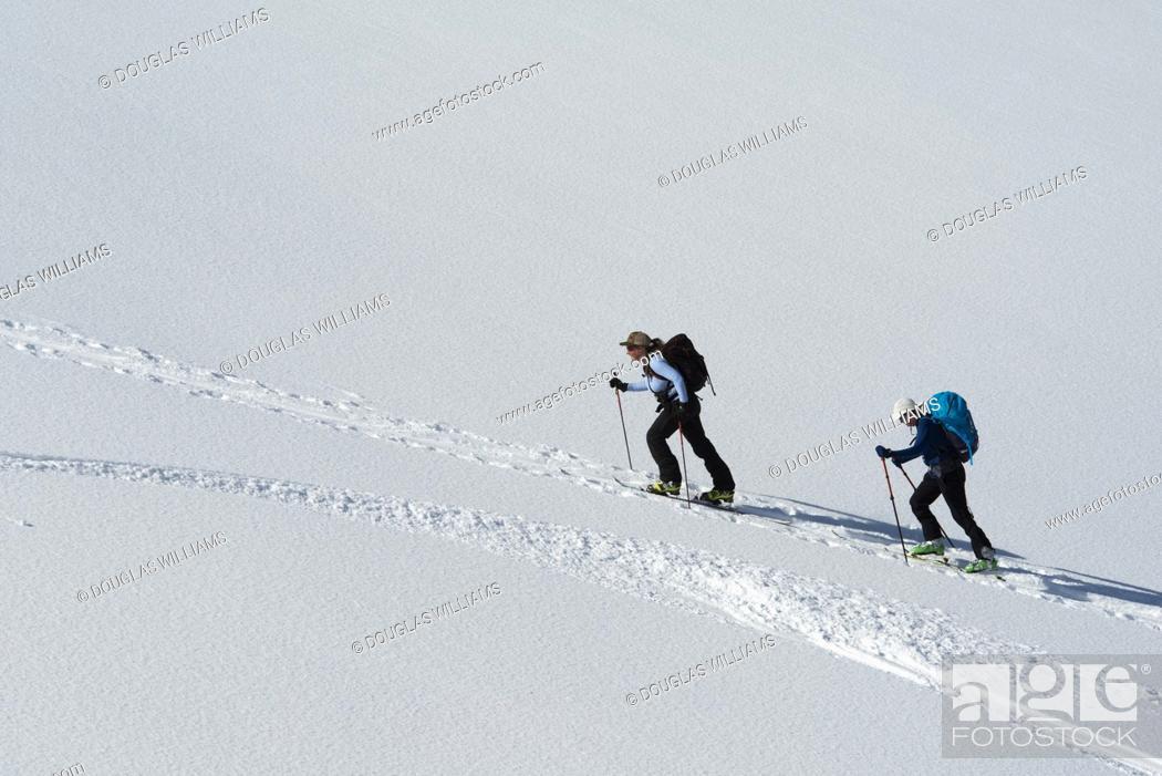 Stock Photo: Two women ski up Parker Ridge, Banff National Park, Alberta, Canada.
