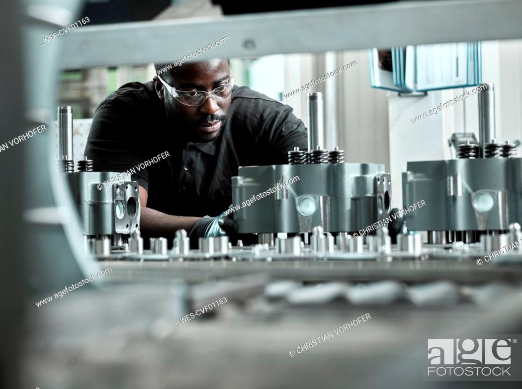 Stock Photo: Young man checking production line on a conveyor belt.