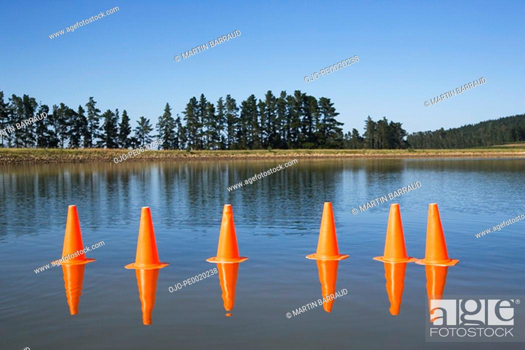 Stock Photo: Traffic cones on water with trees.