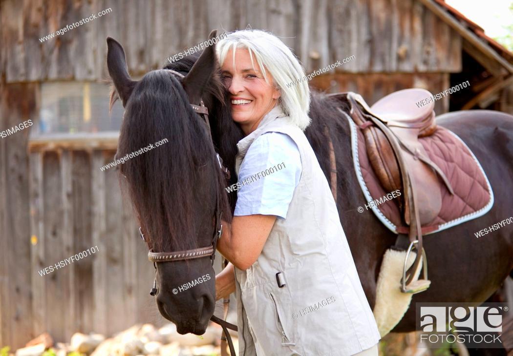 Stock Photo: Germany, Bavaria, Mature woman hugging horse.