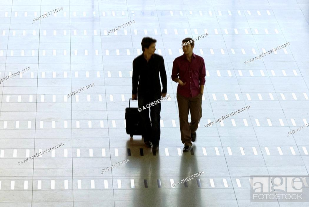 Stock Photo: Mid adult man walking with a young man at an airport.