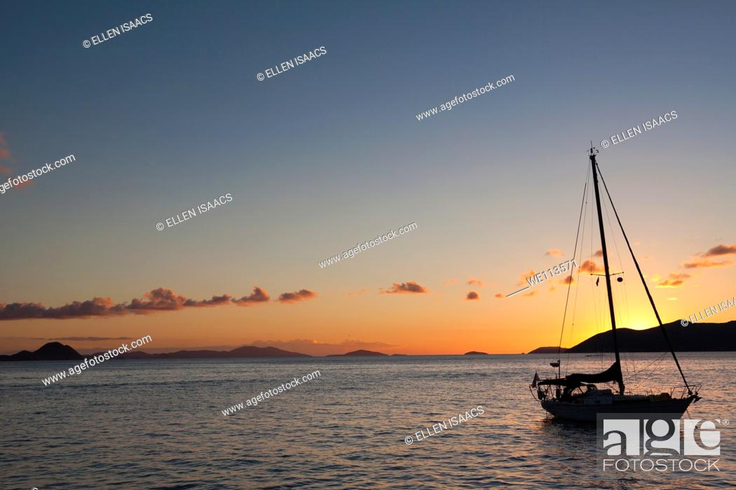 Stock Photo: Silhouette of sailboat moored in water with orange glow of sunset lighting up the clouds and sky in Caribbean.