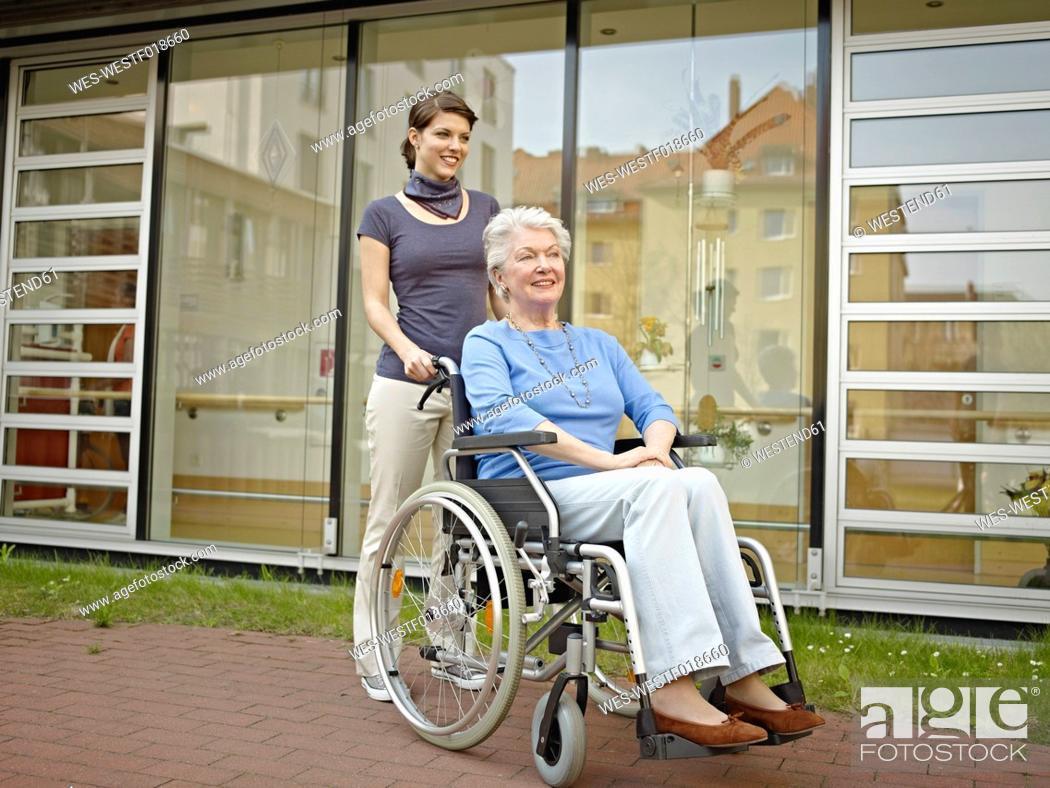 Stock Photo: Germany, Cologne, Women pushing senior women in wheelchair outside of nursing home.
