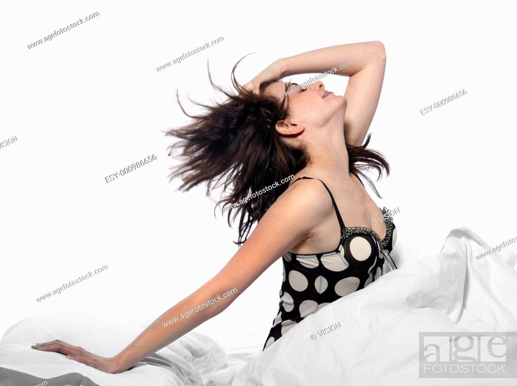 Stock Photo: young woman in a white sheet bed on white background.