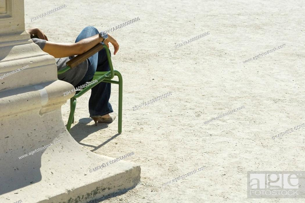 Stock Photo: Woman relaxing in chair in sunny park, cropped view.
