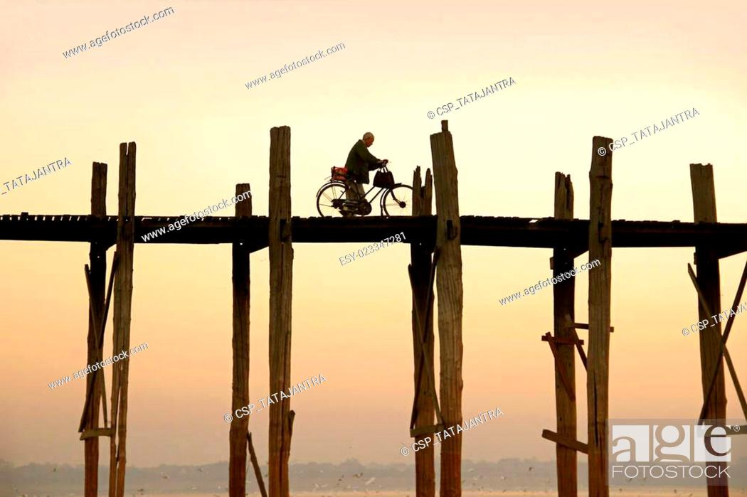 Stock Photo: cyclist is driving over U Bein's Bridge.