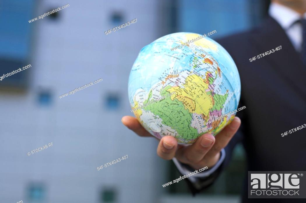 Stock Photo: Hand holding a small earth ball.