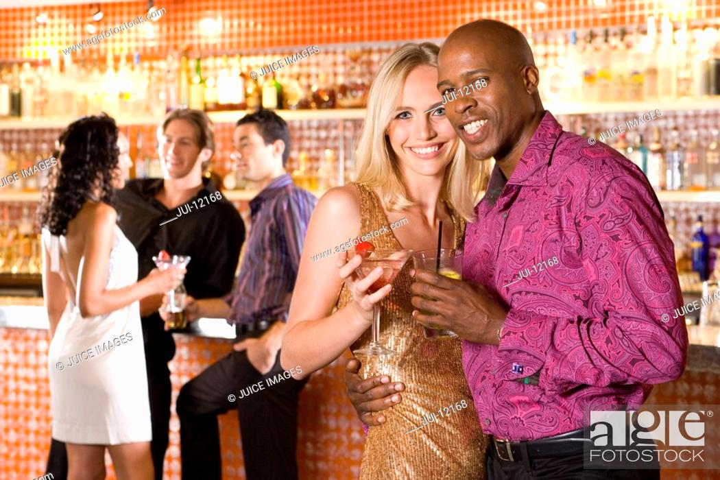 Stock Photo: Young couple arm in arm in bar with drinks, smiling, portrait.