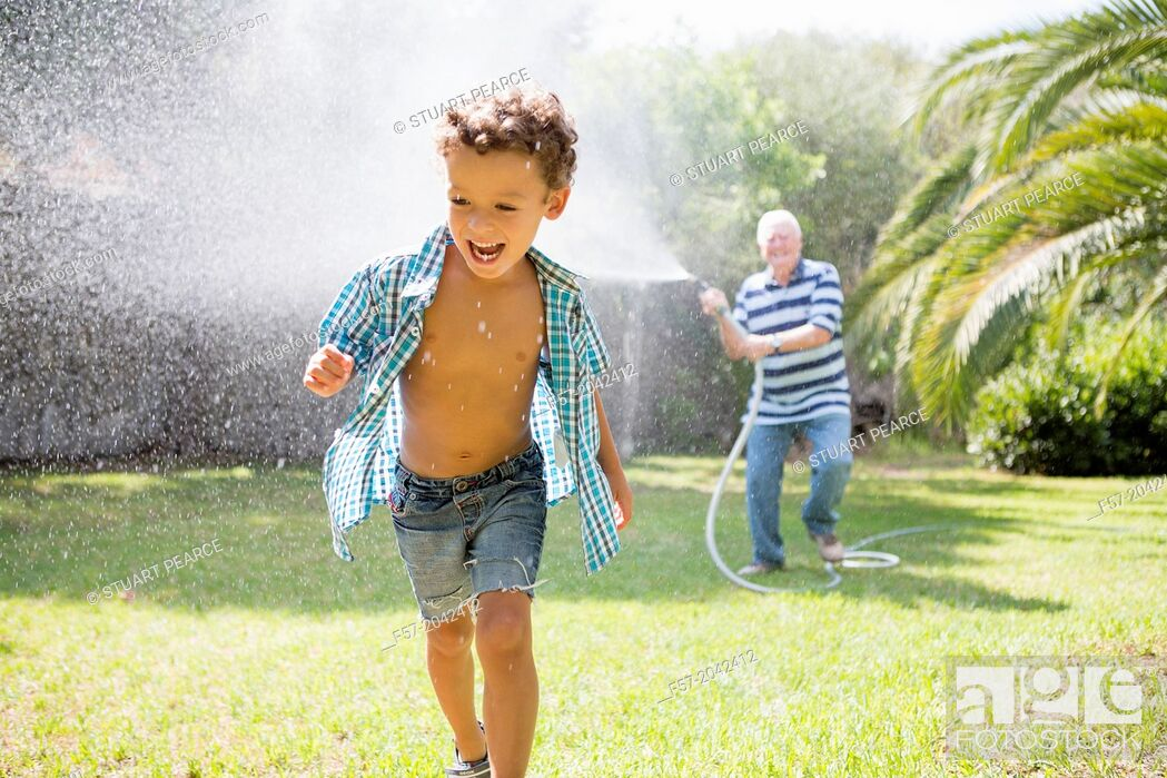 Stock Photo: Young boy playing with his grandfather in the garden.