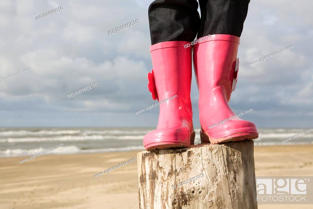 Stock Photo: Child standing on a pole in boots.