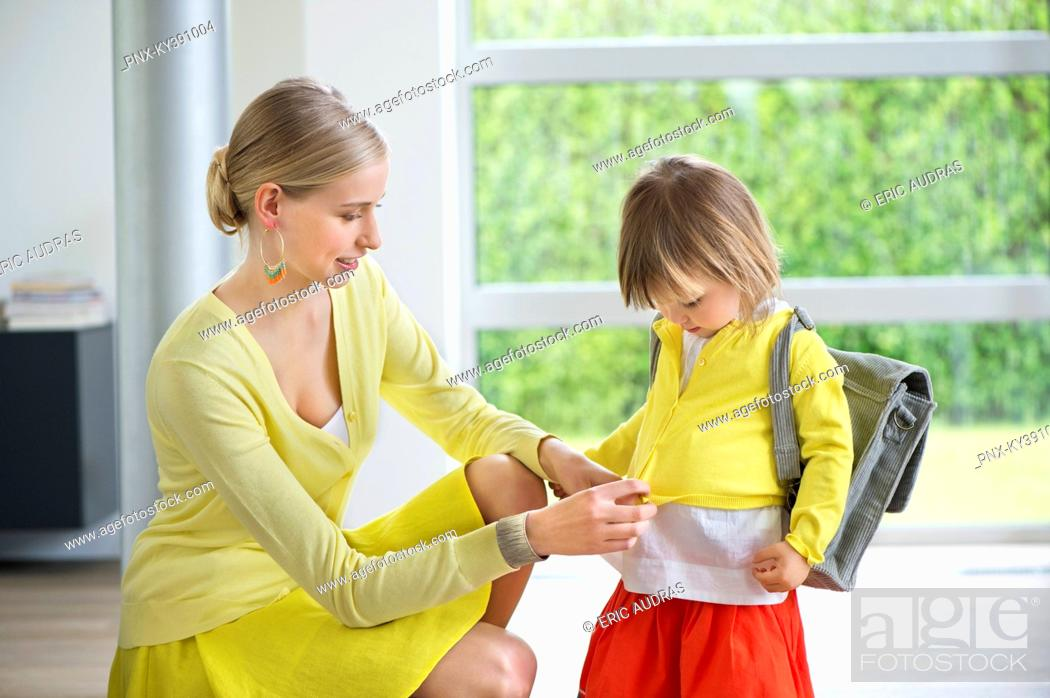 Stock Photo: Woman preparing her daughter for school.