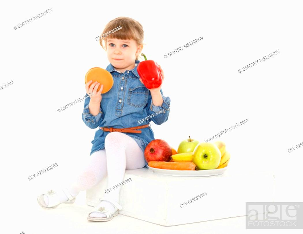 Stock Photo: Little sweet girl with hamburger, fresh fruits and vegetables on a white background. Healthy and unhealthy food. 3 year old.