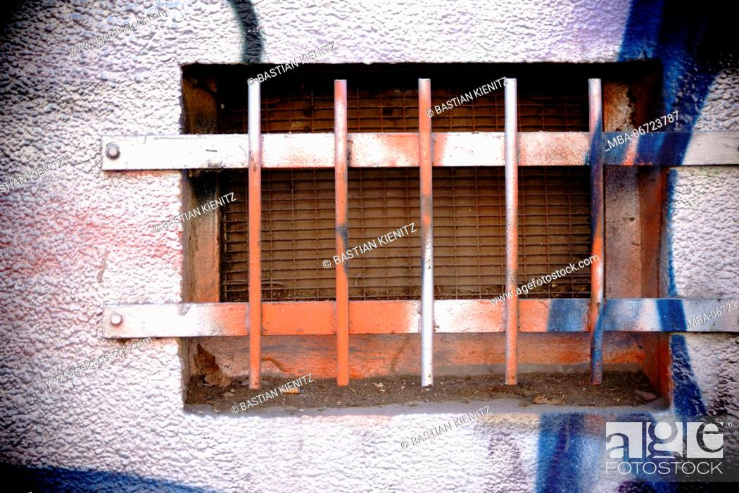 Stock Photo: Close-up of a brightly painted cellar hole with rusted iron bars.