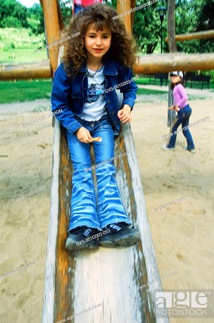 Stock Photo: Young girl playing on a slide.