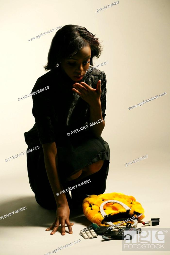 Stock Photo: Young African American woman picking up purse.