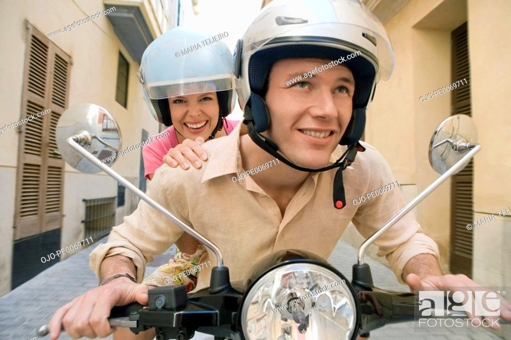 Stock Photo: Man and woman riding scooter.