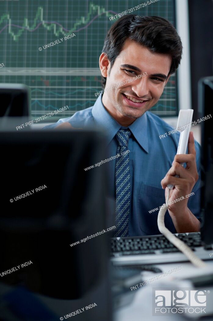 Imagen: Businessman holding phone receiver and smiling.