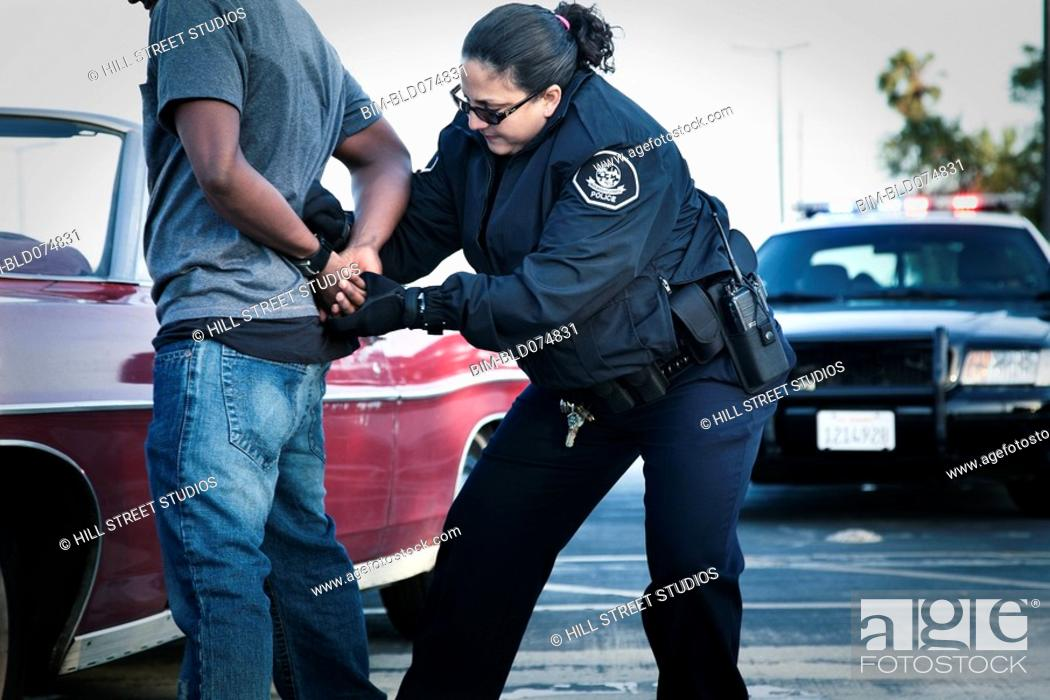 Stock Photo: Hispanic policewoman handcuffing man.