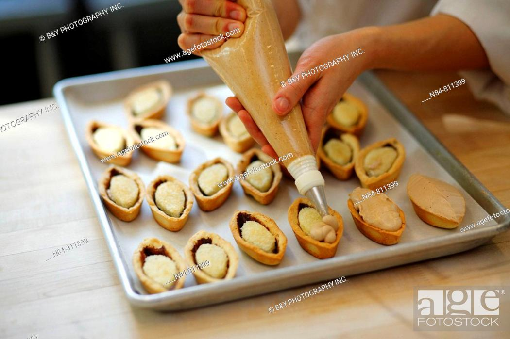 Stock Photo: Pastry chef making small pastries.