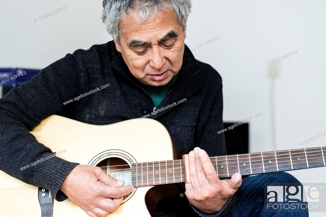 Stock Photo: Tilburg, Netherlands. Middle aged man playing acoustic guitar in his living room.