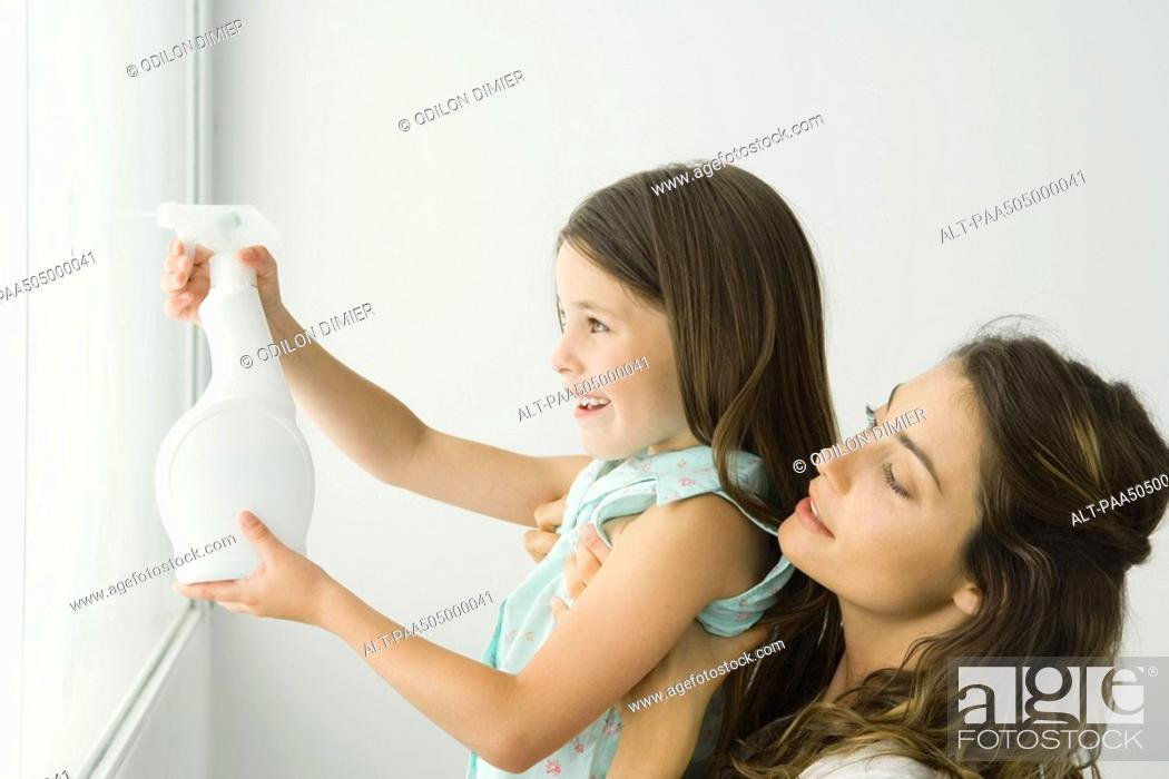 Stock Photo: Little girl cleaning window, mother holding her, both smiling.