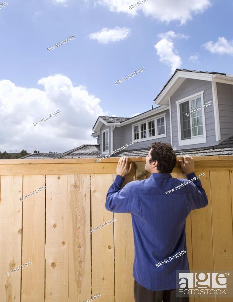 Stock Photo: Hispanic man looking over fence.