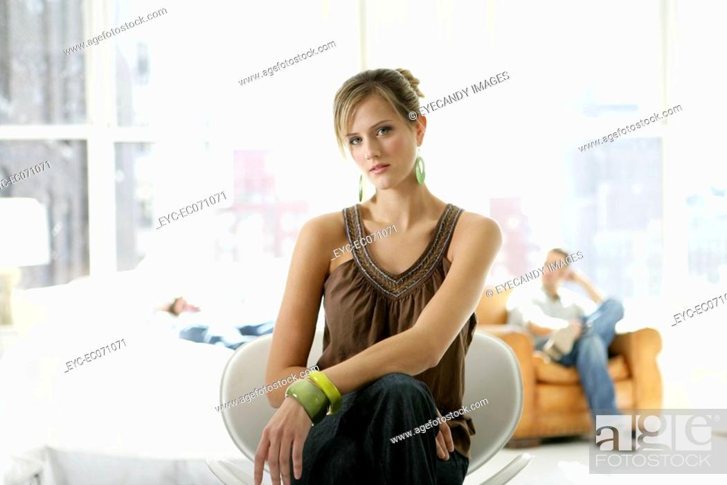 Stock Photo: Young stylish woman sitting in chair with man behind.