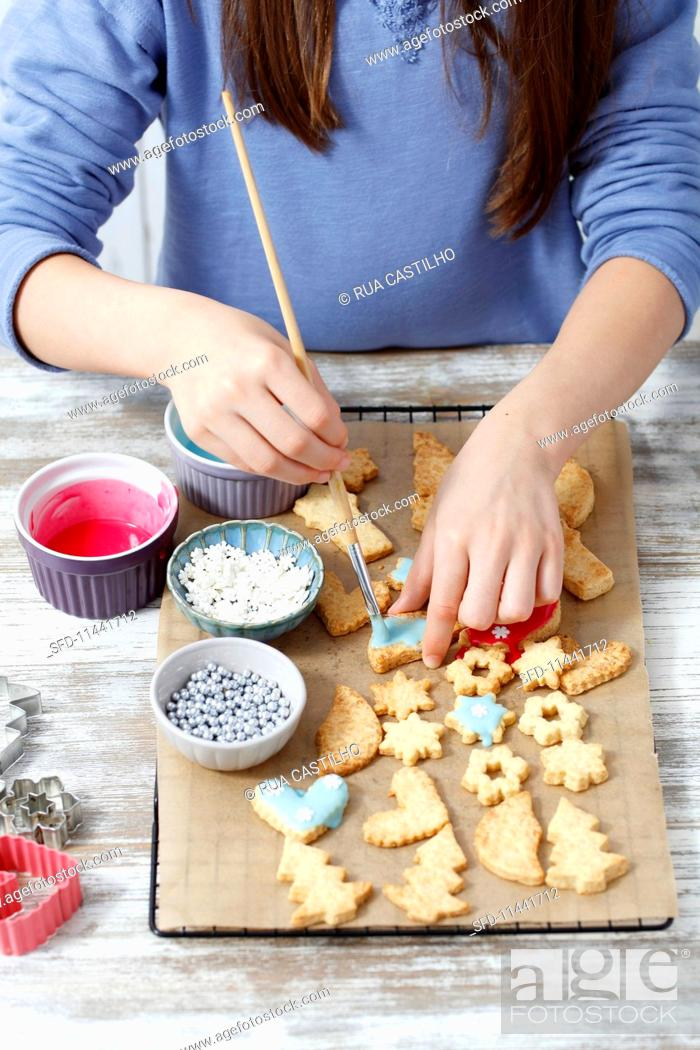 A Girl Decorating Homemade Christmas Biscuits Stock Photo Picture