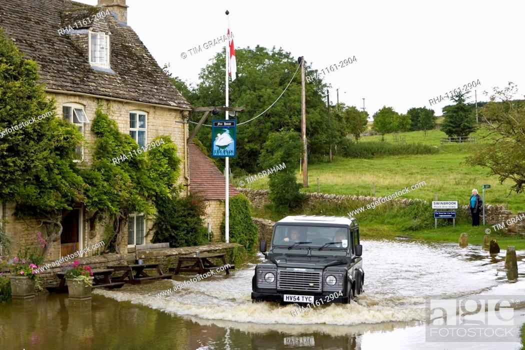 Stock Photo: Four wheel drive car drives through flooded road in Swinbrook, Oxfordshire, England, United Kingdom.