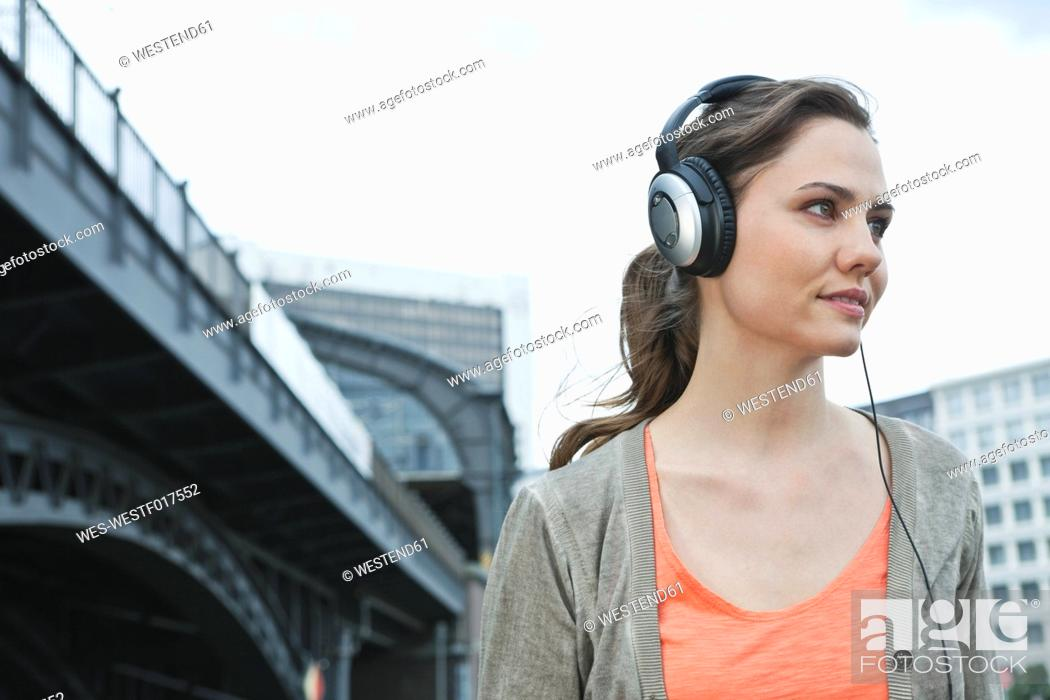 Stock Photo: Germany, Berlin, Woman with headphones listening to music.