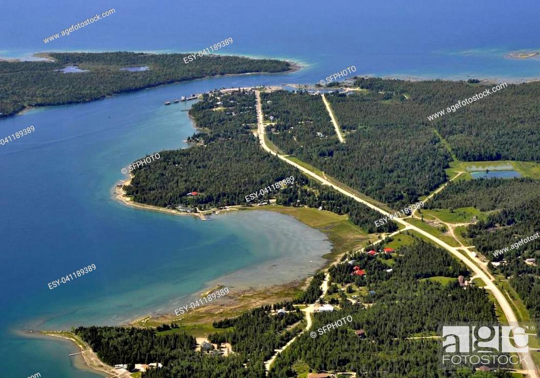 Photo de stock: aerial view of the road through a forest area leading to the ferry dock on the end of the road, vacation cottages along the shore of the lake.