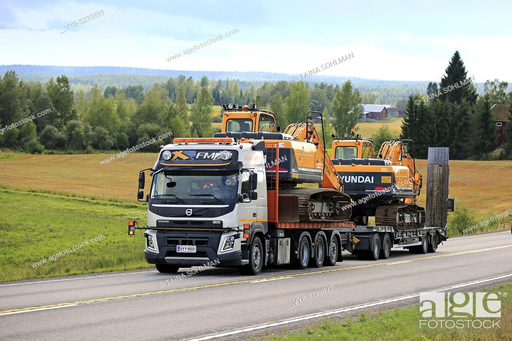 Stock Photo: Jamsa, Finland - August 23, 2018: Volvo FMX truck hauls two Huyndai Robex 180 LC-9 and 160 LC-9 crawler excavators on trailer along road as wide load.
